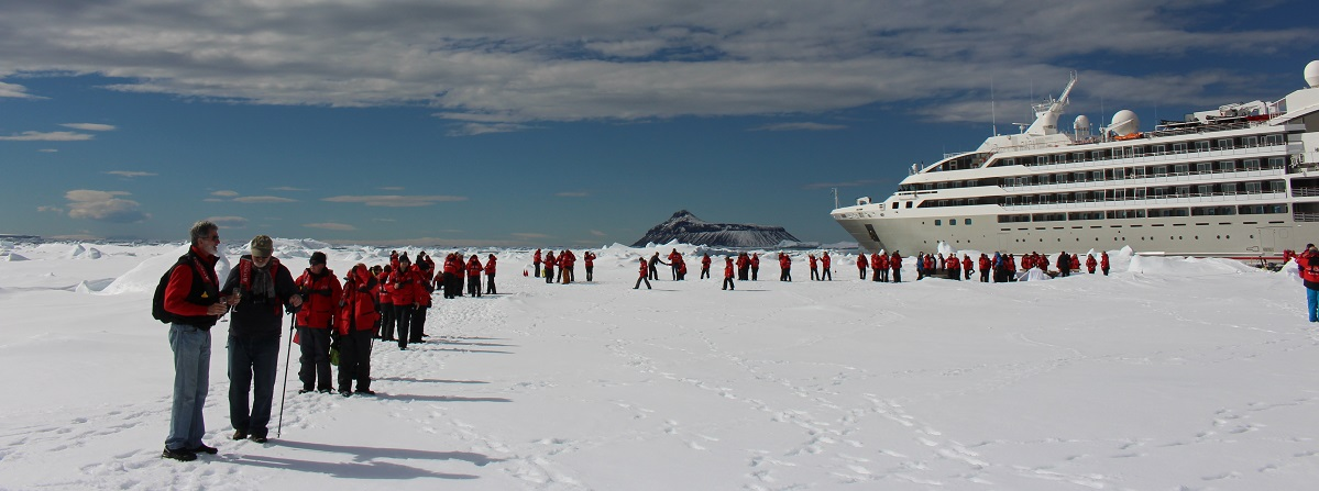 On the ice floe with Cockburn Island in the background. Ponant Antarctic Cruise on Le Soleal